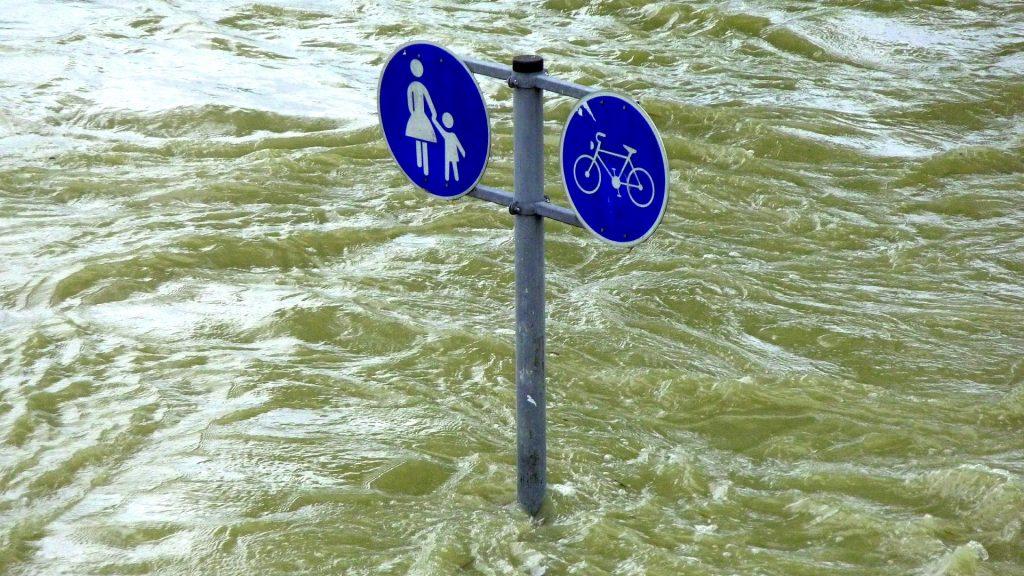 flooded foot- and bike path with trafic signs/ überfluteter Geh- und Radweg, Verkehrszeichen
